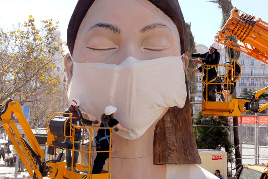 Workers place a mask on the figure of the Fallas festival in Valencia, Wednesday March 11, 2020. The Fallas festival which was due to take place on March 13 has been cancelled over the coronavirus outbreak. For most people, the new coronavirus causes only mild or moderate symptoms, such as fever and cough. For some, especially older adults and people with existing health problems, it can cause more severe illness, including pneumonia.