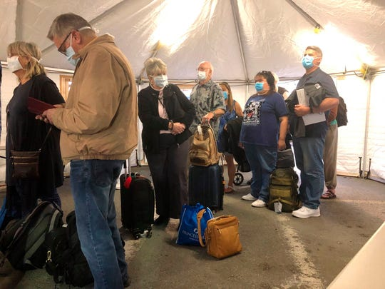 Passengers wait to be screened onshore after coming off the Grand Princess Tuesday. From there, they will be taken to military bases in California, Georgia and Texas to begin a 14-day quarantine.