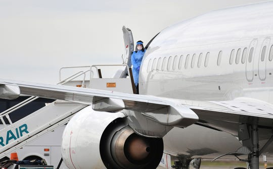 Hazmat-suited medical personnel have been helping to load Grand Princess passengers onto charter planes leaving Oakland International Airport since disembarkation began Monday.