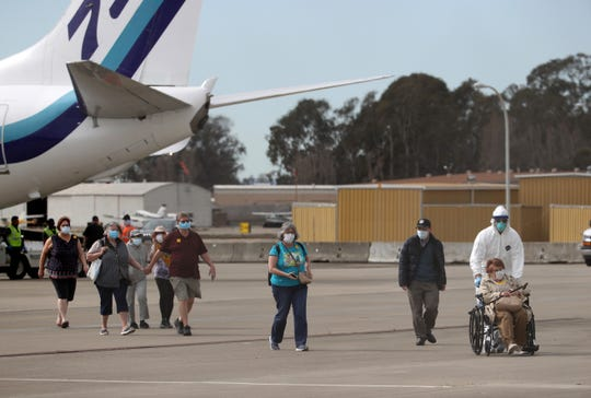 Passengers from the Grand Princess are ushered to charter planes at Oakland International Airport on Tuesday. From there, they will head to military bases in California, Texas and Georgia to begin a 14-day quarantine.