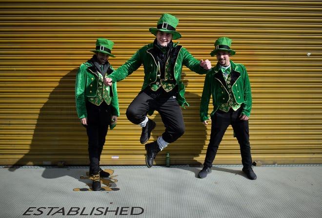 Three attendees of Dublin's 2019 St. Patrick's Day parade in festive attire.