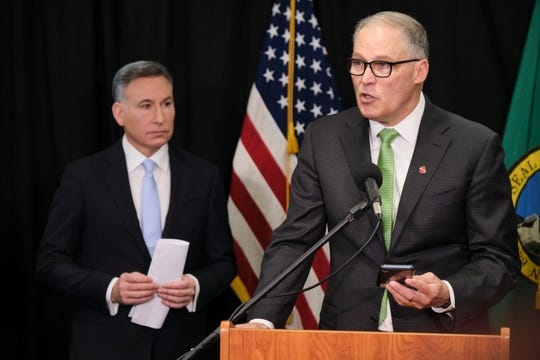 Washington Gov. Jay Inslee talks to reporters while King County Executive Dow Constantine listens, Wednesday, March 11, 2020, during a news conference in Seattle.