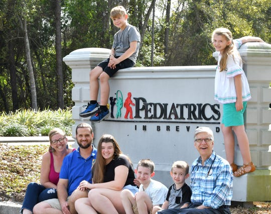 Dr. William Knappenberger of Pediatrics in Brevard with the Armistead family, who have all been patients of his, including parents Melanie and Scott, at left, when they were children. Their children are Baylee, 16, Beau, 7, and Brodie, 4. On the sign is Brandt, 11, and Brooklyn, 9.