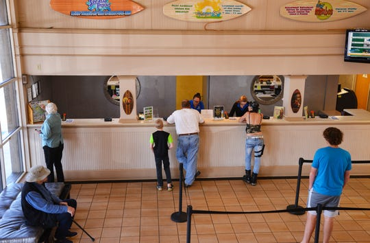 Guests check in Thursday afternoon at the International Palms Resort in Cocoa Beach, which is experiencing reservation cancellations because of coronavirus.