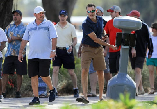 Fans stop at a hand sanitizer station during the first round of The PLAYERS Championship on The Stadium Course at TPC Sawgrass on March 12, 2020, in Ponte Vedra Beach, Florida.
