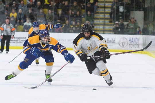 Milton's Nicholas Desouza (6) battles for the puck as Harwood's Tyson Sylvia (17) skates past during the DII boys hockey championship game between the Milton Yellowjackets and the Harwood Union Highlanders at Gutterson Field House on Wednesday night March 11, 2020 in Burlington, Vermont.