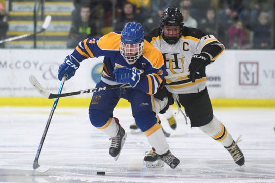 Harwood's Oliver Hammond (11) battles for the puck with Milton's Owen Perry (2) during the DII boys hockey championship game between the Milton Yellowjackets and the Harwood Union Highlanders at Gutterson Field House on Wednesday night March 11, 2020 in Burlington, Vermont.