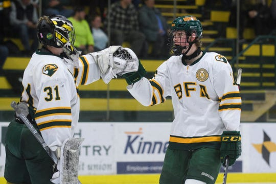 BFA's Nathan Benoit (16) high fives goalie Daniel Ellis (31) during the DI boys hockey championship game between the Stowe Raiders and the BFA St. Albans Bobwhites at Gutterson Field House on Wednesday night March 11, 2020 in Burlington, Vermont.