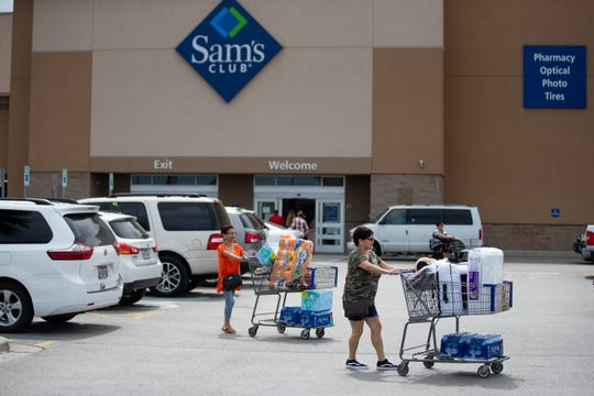 People leave Sam's Club with water and paper goods in Corpus Christi amid growing COVID-19 concerns on Thursday, March 12, 2020.