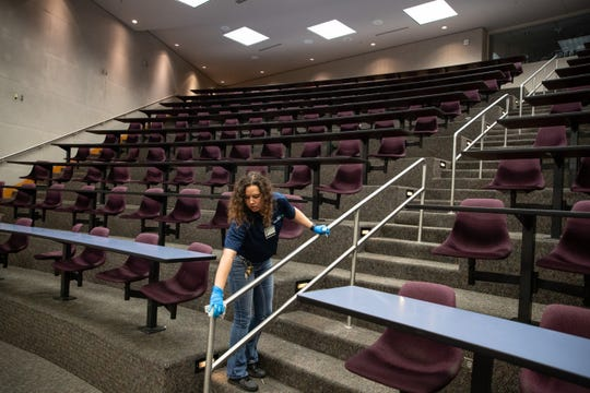 A worker cleans a class room at Texas A&M University-Corpus Christi as they clean twice a day to do COVID-19 precautions on Tuesday, March 12, 2020.