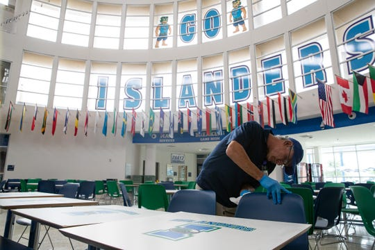 A worker cleans tables and chairs in the University Center's rotunda at the Texas A&M University-Corpus Christi as they clean twice a day to do COVID-19 precautions on Tuesday, March 12, 2020.