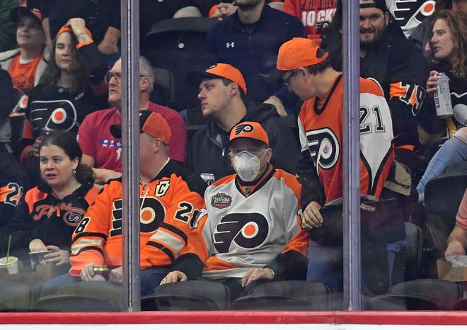 A Flyers fan wears a mask during the first period during Tuesday's 2-0 loss to the Boston Bruins at Wells Fargo Center.