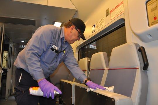PATCO HI-Speedline  equipment custodian Eulisis Delgado sanitizes train seats on its S. Jersey-Philadelphia  commuter line Wednesday to help prevent the potential spread of the Coronavirus