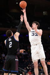 Xavier forward Zach Freemantle (32) shoots over DePaul forward Jaylen Butz (2) during the first half of an NCAA college basketball game in the first round of the Big East men's tournament Wednesday, March 11, 2020, in New York.