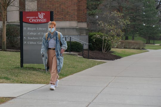 Dot Tsolometes wears a mask while walking around the University of Cincinnati's campus, Wednesday, March 11, 2020. After this Friday, the university will go strictly online and stop having in person lectures due to the coronavirus.