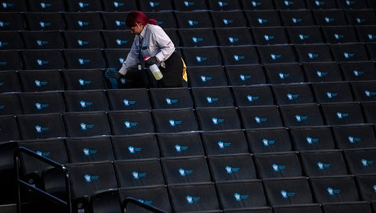 A worker disinfects seats prior to the start of the second round of the 2020 Atlantic 10 men's basketball tournament at Barclays Center on March 12, 2020 in the Brooklyn borough of New York City. The tournament was canceled amid growing concerns of the spread of Coronavirus (COVID-19).