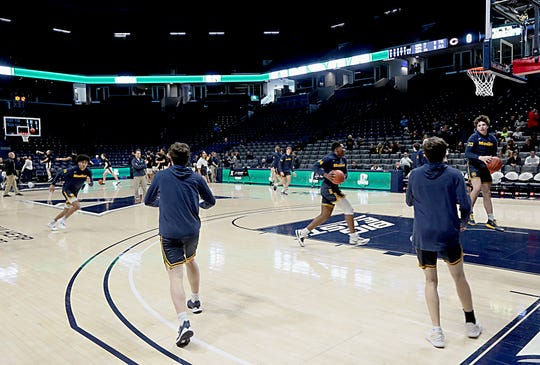 The Moeller High School basketball team warms up moments before tip-off in a nearly empty Cintas Center for their Division I regional semifinal boys basketball game Wednesday, March 11, 2020.