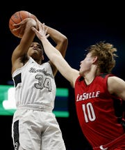 Lakota East High School's Nate Johnson shoots against La Salle's Ayden Schneider during their Division I regional semifinal boys basketball game at the Cintas Center in Cincinnati Wednesday, March 11, 2020.