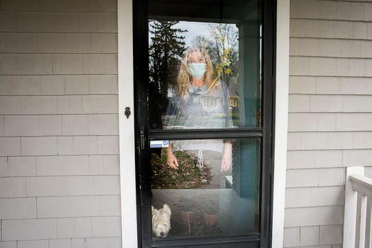 Connie Smith-Monahan looks out of the front door of her Madisonville home. She is now quarantined as she waits for answers regarding testing for the new coronavirus.