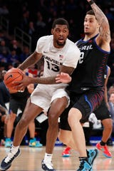 Xavier forward Naji Marshall (13) drives around DePaul forward Jaylen Butz (2) during the first half of an NCAA college basketball game in the first round of the Big East men's tournament Wednesday, March 11, 2020, in New York.