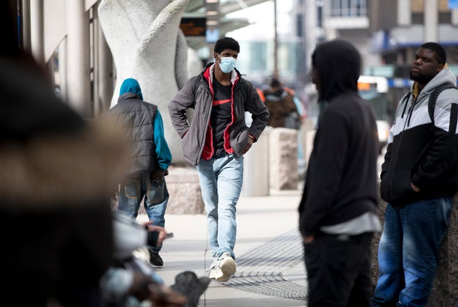 Mike Godby, of Finneytown, walks through the bus stop wearing a precautionary mask in Downtown Cincinnati on Thursday, March 12, 2020.