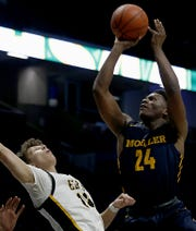 Moeller High School forward Alex Williams scores against Centerville forward Rich Rolf during their Division I regional semifinal boys basketball game at the Cintas Center in Cincinnati Wednesday, March 11, 2020.