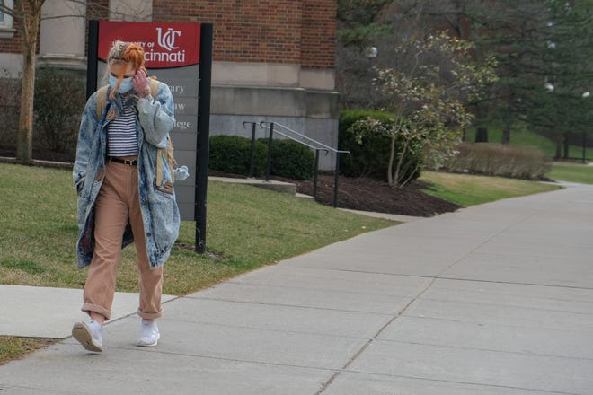 Dot Tsolometes wears a mask while walking around the University of Cincinnati's campus, Wednesday, March 11, 2020.