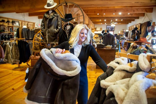 Store manager Laura Fischer arranges products at  Overland Sheepskin Co. in Fairfield Tuesday, Feb. 18, 2020.