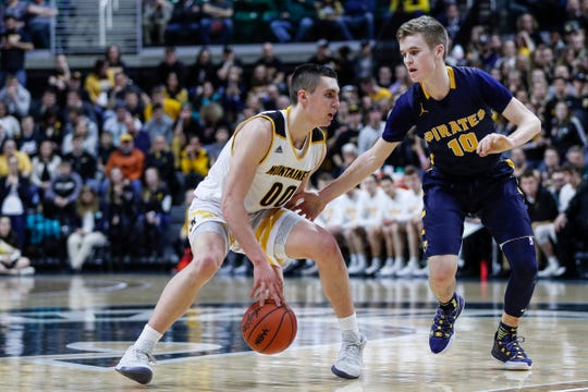Iron Mountain's Foster Wonders (00) dribbles against Pewamo-Westphalia's Hunter Hengaesbach (10) during the first half of MHSAA Division 3 final at the Breslin Center in East Lansing, Saturday, March 16, 2019.
