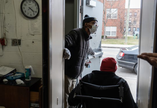 Detroit Rescue Mission Ministries resident specialist Bobbie James lets a man out while wearing a mask and gloves as he mans the entrance to the shelter in Detroit on Thursday, March 12, 2020 as people come in after being checked at the metal detectors.