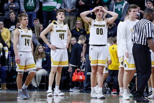 Iron Mountain players Marcus Johnson (14), Tony Feira (40) and Foster Wonders (00) react to a call in the last seconds of the second half of MHSAA Division 3 final against Pewamo-Westphalia at the Breslin Center in East Lansing, Saturday, March 16, 2019.