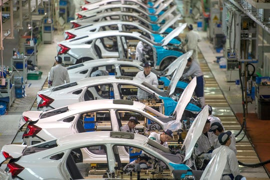 In this Feb. 6, 2017 photo, workers assemble Honda Civics on an assembly line at a Dongfeng Honda automotive plant in Wuhan in central China's Hubei province.