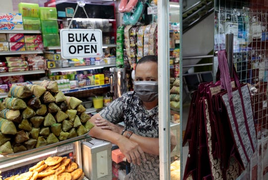 A snack vendor wearing a face mask looks out from his shop as Health officials spray disinfectant in the wake of coronavirus outbreak in Jakarta, Indonesia, Thursday, March 12, 2020.