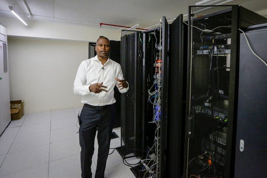 In this photo taken on Thursday, March 5, 2020, Abubakr Salih Babiker, a climate scientist at the Intergovernmental Authority on Development's Climate Prediction and Applications Center, shows server racks containing a supercomputer in Nairobi, Kenya.