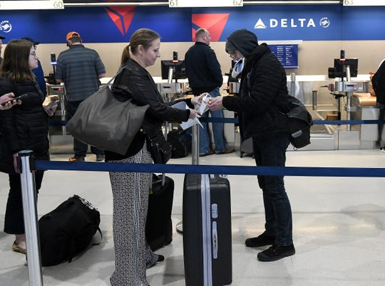 Lisa Pierchala and Russell Taylor, both of Detroit, use hand sanitizer in line at the Delta counter about to head to New Orleans at Detroit Metropolitan Wayne County Airport in Romulus.