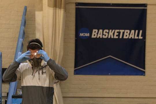 Taylor Michel, director of operations of the Disinfecting Technologies Group, prepares to disinfect the arena following an NCAA Division III men's basketball game at Goldfarb Gymnasium at Johns Hopkins University last Friday in Baltimore, Md. On Wednesday the NCAA announced the Division I tournament would be closed to fans.