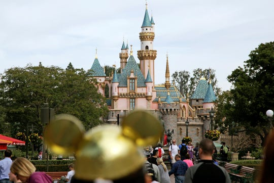 Visitors walk toward Sleeping Beauty's Castle in the background at Disneyland Resort in Anaheim, Calif. on Jan. 22, 2015.