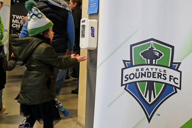 A young fan makes use of a hand-sanitizing station at CenturyLink Field prior to an MLS soccer match between the Seattle Sounders and the Chicago Fire in Seattle.