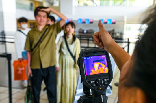 A tourist preparing to depart on a flight from the A.B. Won Pat International Airport gets a thumbs-up from Department of Public Health and Social Services nurse Leonisa Benavente after being subjected to a thermal imaging scan March 12.