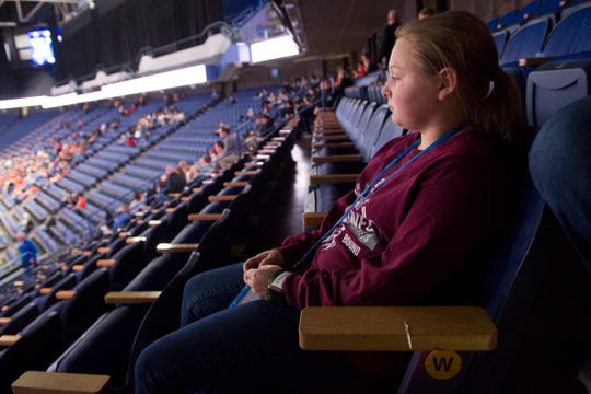 Kimberly Shelton, 12, watches the Sacred Heart vs South Laurel game of the KHSAA Girls' Basketball Sweet 16 after finding out that the tournament would be suspended following the game to try to stem the spread of the coronavirus, not allowing her to see her cousin Henderson County's Sadie Wurth (15) take the floor at Rupp Arena in Lexington, Ky., Thursday afternoon, March 12, 2020.
