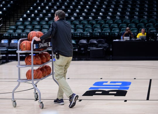 A stadium worker clears basketballs from the floor at Bankers Life Fieldhouse on Thursday morning. The rest of the Big Ten Tournament was canceled.