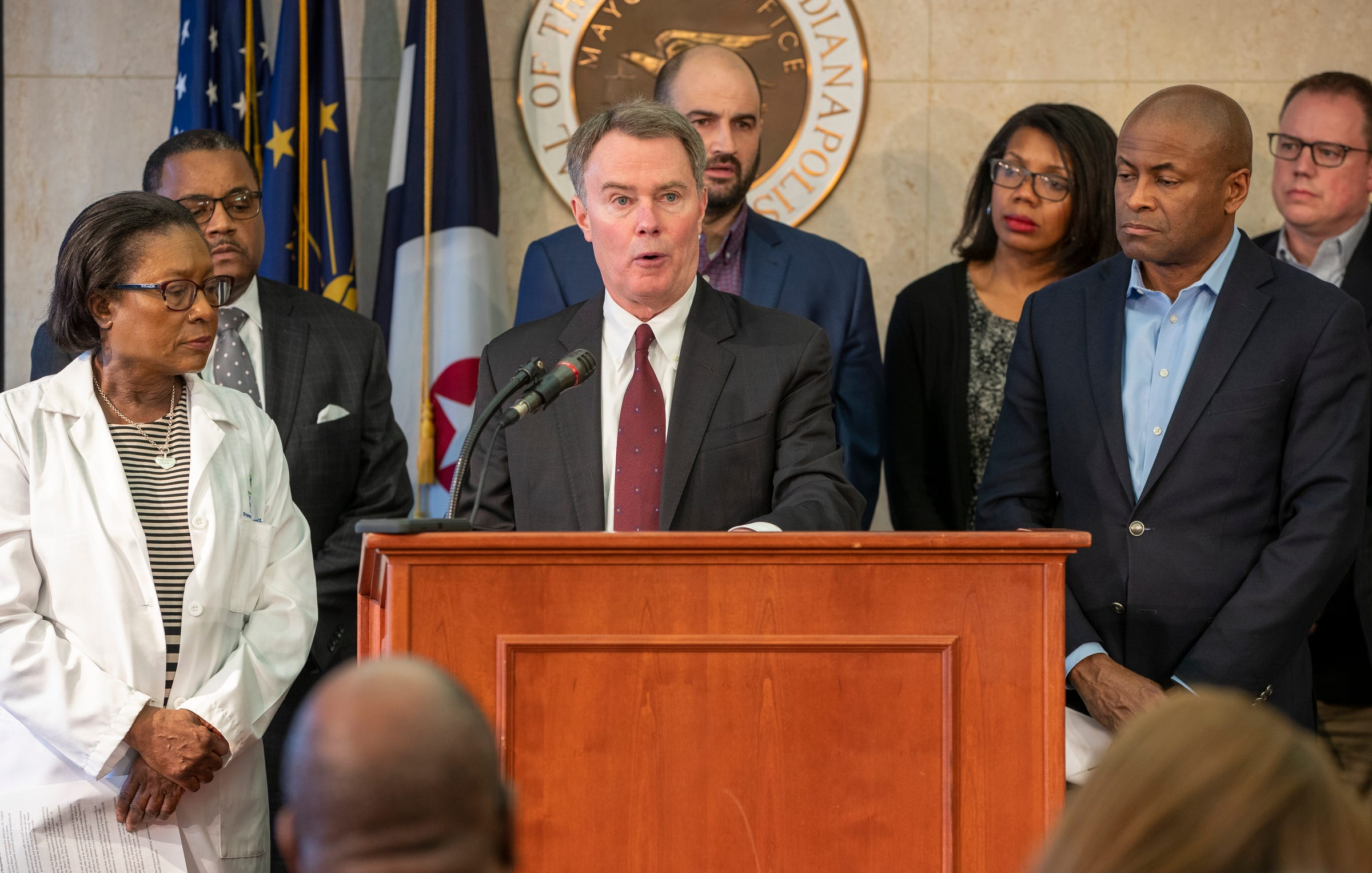 Indianapolis Mayor Joe Hogsett, surrounded by educators, medical personnel, and other city officials, talks about the decision to close county schools amid fears about COVID-19,  Indianapolis, Thursday, March 12, 2020. The move is a preemptive one, and currently no students or faculty have the Coronavirus.