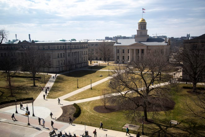 University of Iowa students walk on campus, Thursday, March 12, 2020, on the Pentacrest and the Old Capitol Building in Iowa City, Iowa.