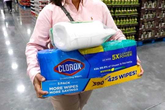 A Costco customer takes advantage of the grand opening of a new store in Ridgeland, Miss., to stock up on water, bath tissue and cleaning supplies including disinfecting wipes to help deal with coronavirus, Thursday, March 12, 2020. For most people, the new coronavirus causes only mild or moderate symptoms. For some it can cause more severe illness.