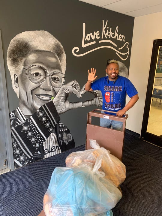 Jacoby Yarbro at The Love Kitchen, which his grandmother Helen, shown prominently in the mural behind him, founded with her twin sister, Ellen. March 5, 2020.