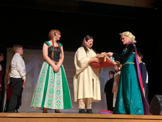 Chloe Wise as 'Anna', Addison Goddard as the 'Bishop' and Ferryn Wright as 'Elsa' during the coronation scene in 'Disney Frozen Jr.' at South Doyle Middle School on March 7, 2020.