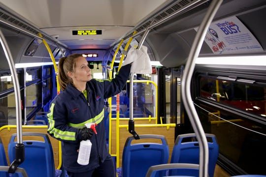 Jessica Conley, a utility worker for CityBus, wipes down the hand railings on a bus with a disinfectant solution, Thursday, March 12, 2020 at the CityBus' administrative offices in Lafayette.