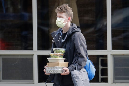 In this March 11, 2020 photo, a worker at the Life Care Center in Kirkland, Wash., near Seattle, wears a mask and stethoscope as he carries food in the parking lot of the facility. The nursing home is at the center of the outbreak of the COVID-19 coronavirus in Washington state. (AP Photo/Ted S. Warren)