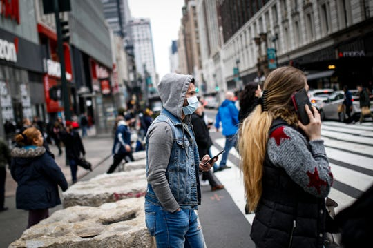 A pedestrian uses his phone while wearing a face mask in New York's Herald Square, Thursday, March 12, 2020. Mayor Bill de Blasio said Thursday he will announce new restrictions on gatherings to halt the spread of the new coronavirus in the coming days, but he hopes to avoid closing all public events such as Broadway shows. (AP Photo/John Minchillo)