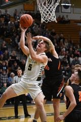 Howell's Peyton Ward is fouled by Fenton's Luke Curran during a district semifinal basketball game on Wednesday, March 11, 2020.